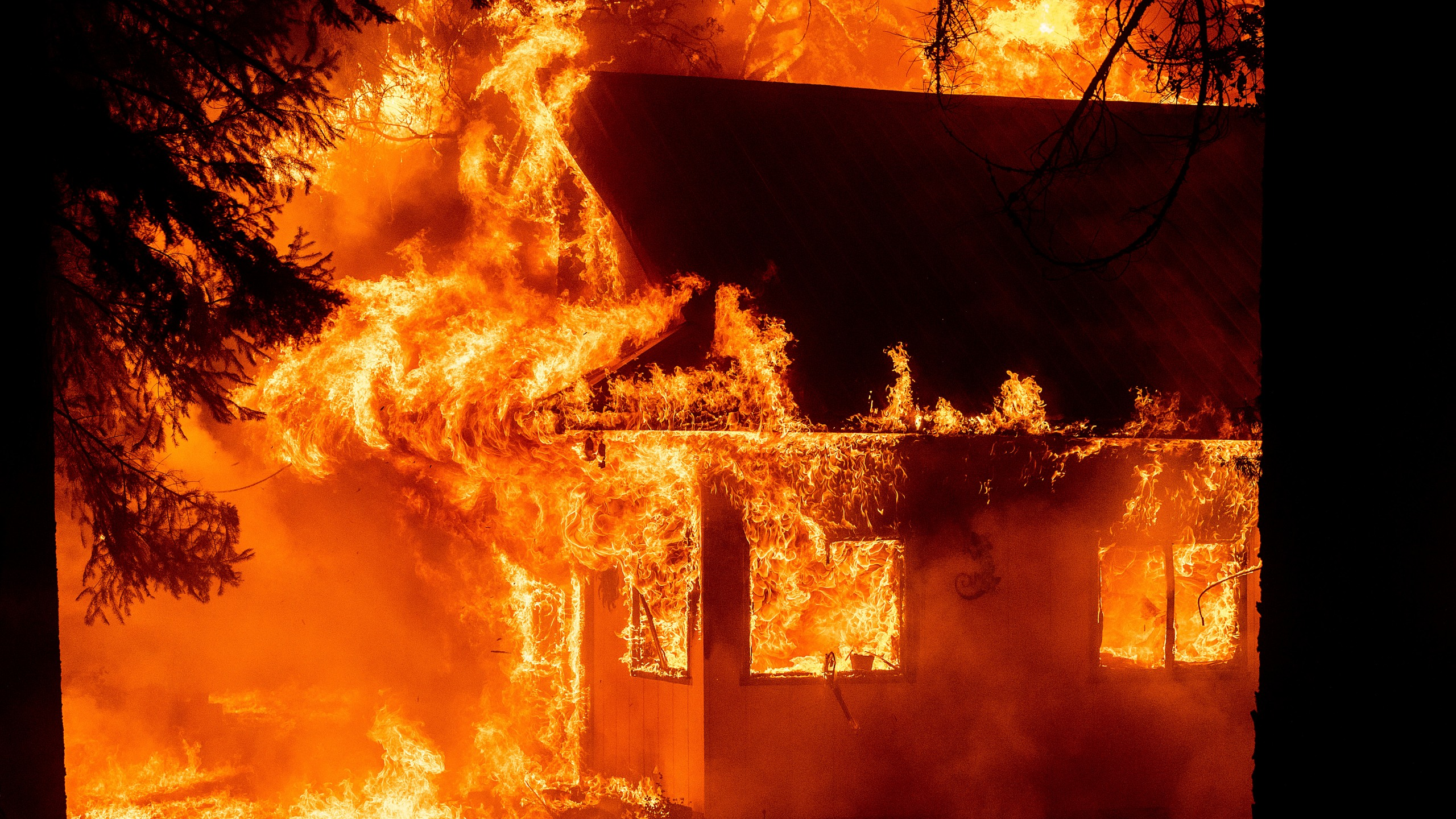 California's largest fire burns homes as blazes torch West