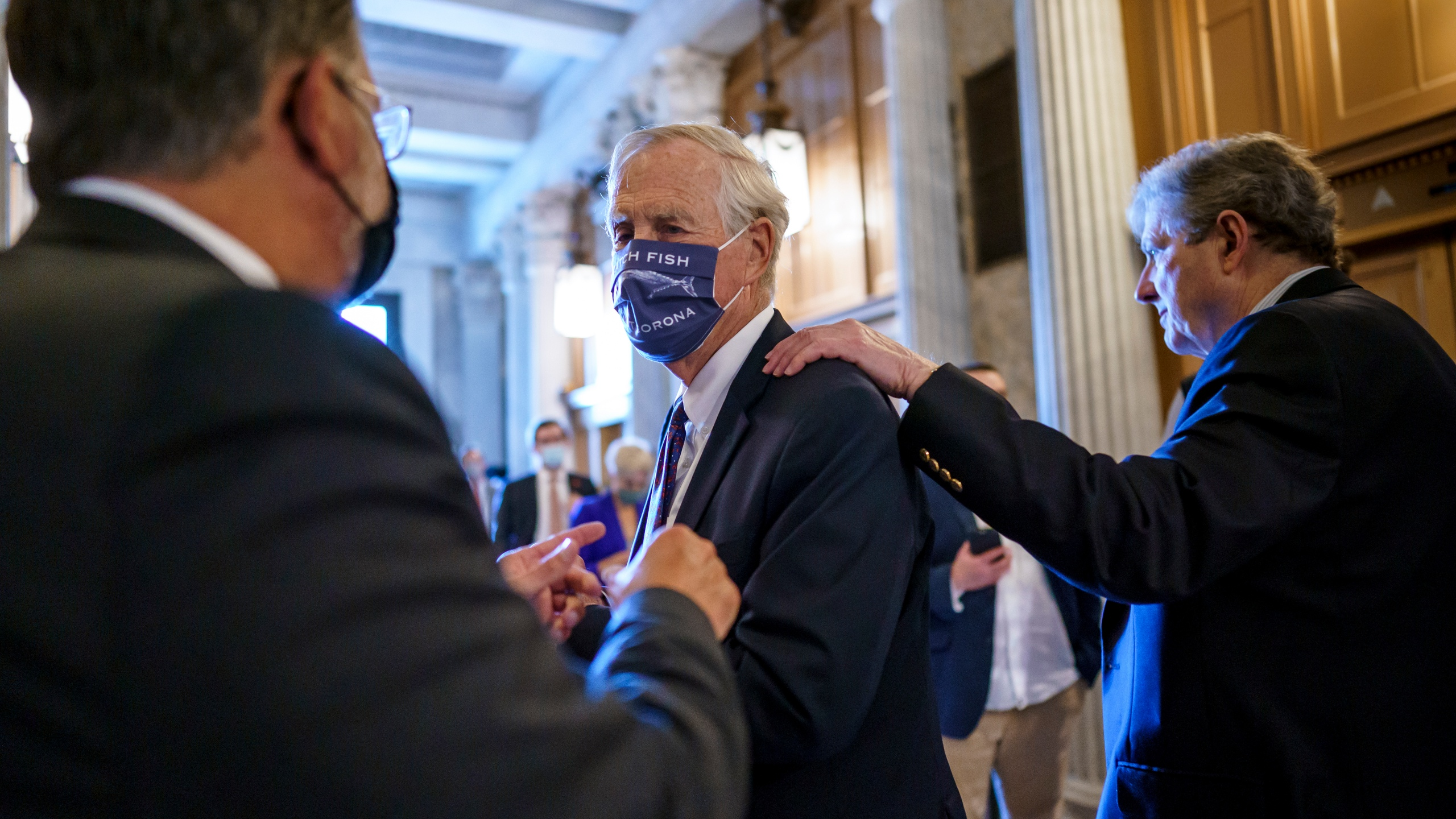 Sen. Angus King, I-Maine, center, speaks with Sen. Gary Peters, D-Mich., left, while Sen. John Kennedy, R-La., walks by at right, as the Senate votes to formally begin debate on a roughly $1 trillion infrastructure plan, a process that could take several days