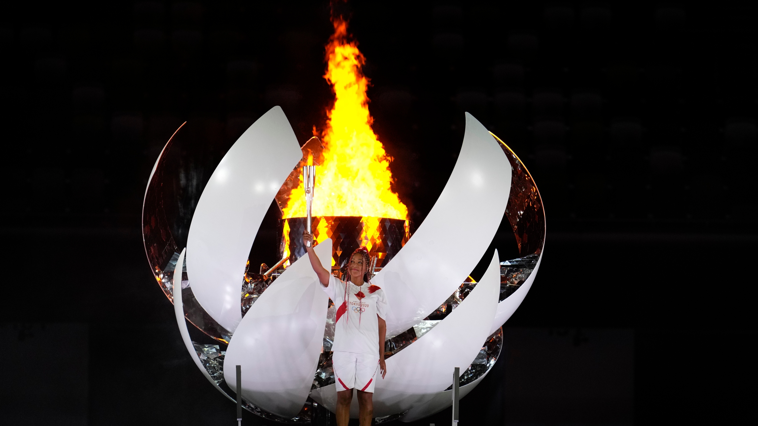 Japan's Naomi Osaka lights the cauldron during the opening ceremony in the Olympic Stadium at the 2020 Summer Olympics, in Tokyo, Japan.